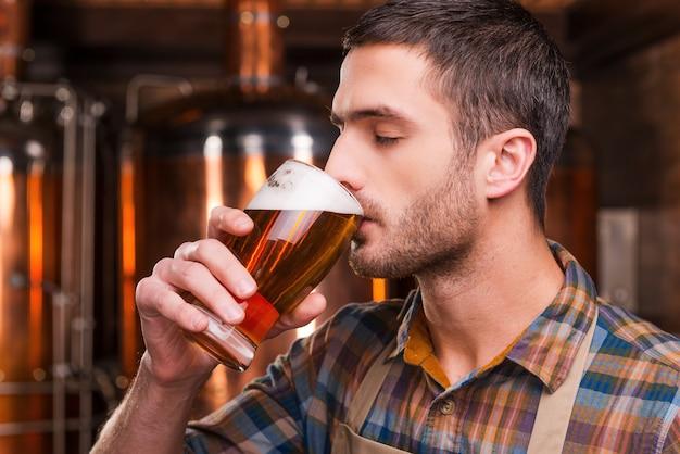 Degustação de cerveja fresca. bonito e jovem cervejeiro de avental degustando cerveja fresca e mantendo os olhos fechados em frente a recipientes de metal