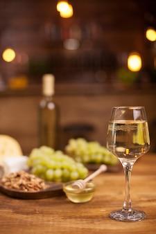 Degustação de vinhos em restaurante vintage com gorgonzola em mesa de madeira rústica. uvas frescas.