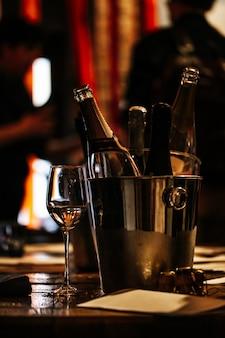 Degustação de vinhos: em uma mesa de madeira há um balde de prata para refrigerar vinhos com garrafas abertas de champanhe e uma taça de vinho.