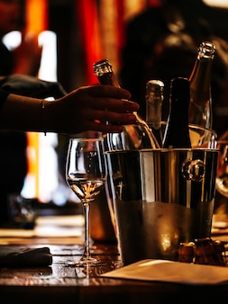 Degustação de vinhos: há uma taça de vinho sobre uma mesa de madeira e um balde de prata para refrigerar vinhos