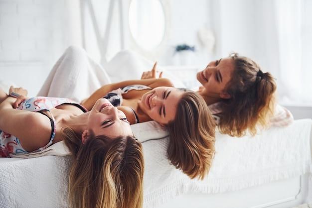 Deitada na cama com o cabelo solto. felizes amigas se divertindo na festa do pijama no quarto.