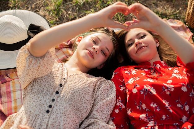 Deitada na grama, belas mulheres jovens com gestos de mão