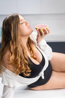 Deitada na mesa da cozinha, mulher jovem e gorda segurando uma toranja fresca na mão, sentindo o cheiro dela.