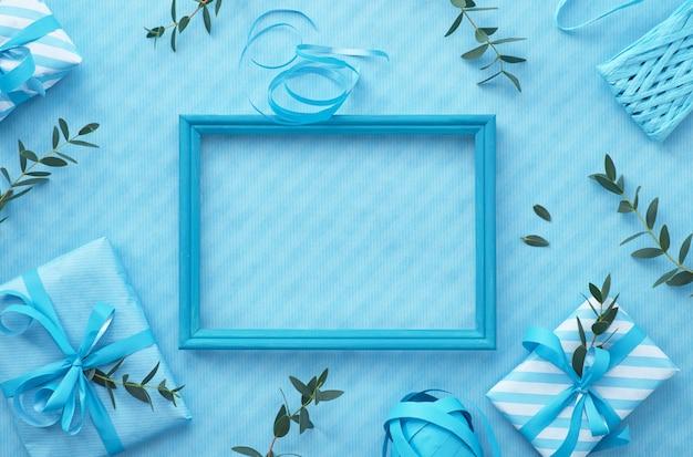 Deitado em tons de azul claro com caixas de presente embrulhadas, decoradas com galhos de eucalipto.