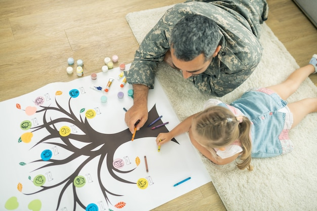 Deitado no chão. vista superior de pai carinhoso e filha deitados no chão e pintando a árvore genealógica