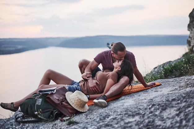 Deitando para um beijo. o jovem casal decidiu passar as férias de forma ativa na beira de uma linda rocha com um lago ao fundo.