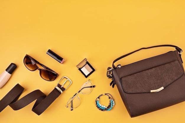 Deite-se com acessórios de moda feminina na parede amarela. moda, blog de beleza online, estilo de verão, conceito de compras e tendências. vista do topo