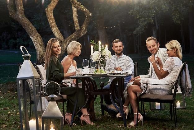 Deixe as velas acenderem naquela noite. grupo de amigos adultos tem um descanso e uma conversa no quintal do restaurante à noite.