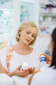 Deixe-me escolher. mulher madura alegre olhando para baixo enquanto escolhe vitaminas