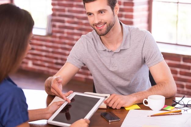 Deixe-me mostrar todos os recursos. duas pessoas alegres em roupas casuais sentadas frente a frente à mesa enquanto o homem aponta o tablet digital e sorri