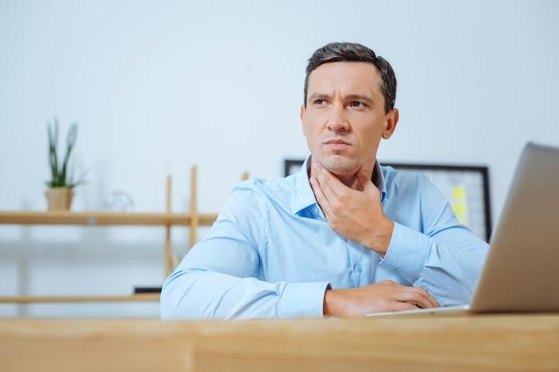 Deixe-me pensar. homem atencioso franzindo a testa e tocando o pescoço enquanto usa o computador