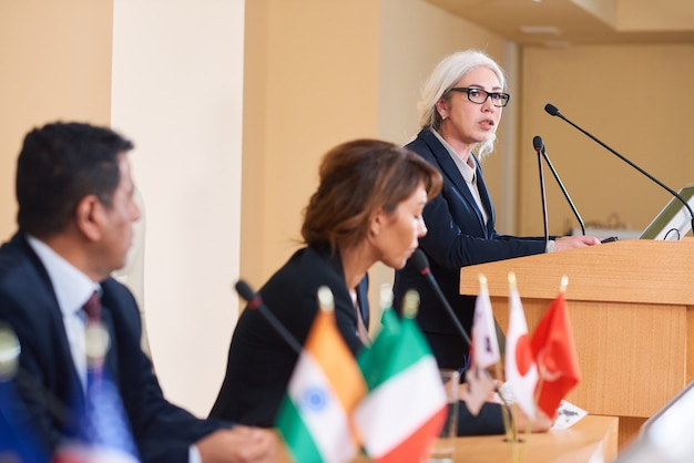 Delegada confiante em trajes formais ao lado da tribuna na frente de colegas estrangeiros durante seu discurso na cúpula