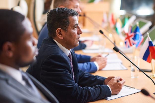 Delegado árabe maduro em trajes formais falando no microfone enquanto discursa em uma conferência de negócios ou cúpula política