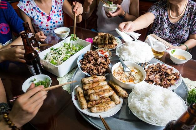 Deleitando-se com a família em comida tradicional vietnamita