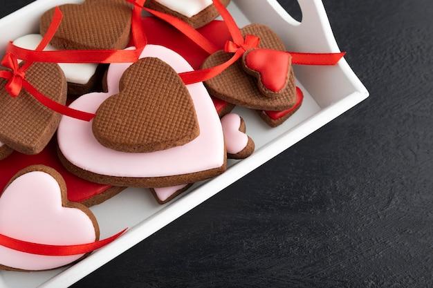 Deleite do dia dos namorados. deliciosos biscoitos caseiros em forma de coração em fundo preto close-up.