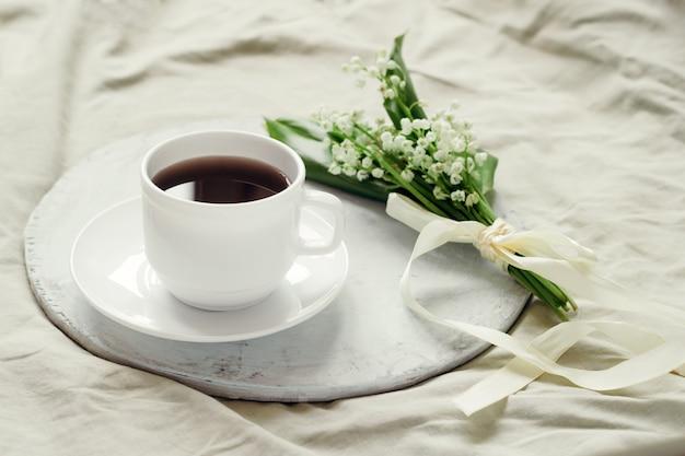 Delicada buquê de lírios frescos do vale decorado com fita de seda e café acabado de fazer