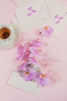 Delicada composição flatlay com uma xícara de chá matinal, uma sacola rosa cheia de flores roxas de orquídea e um envelope vazio na superfície rosa claro