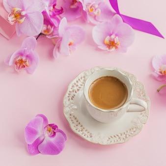 Delicada composição flatlay com xícara de café matinal com leite ou cappuccino, sacola de presente rosa e flores de orquídea em fundo rosa claro