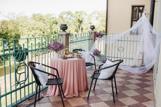 Delicada mesa de chá matinal com flores lilás no castelo nesvizh, colheres antigas e pratos na mesa com toalha rosa.