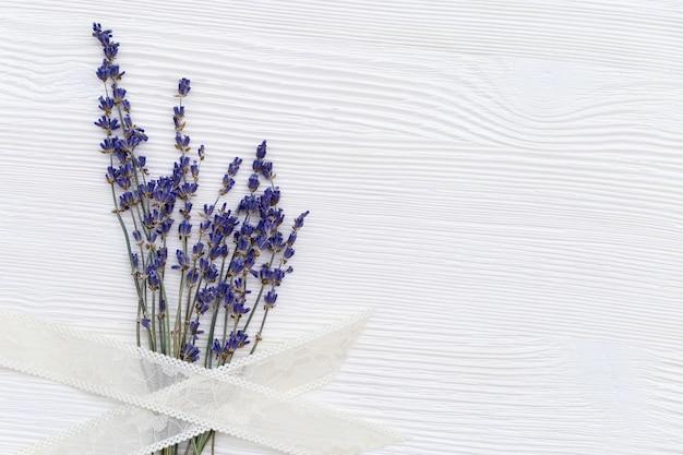 Delicadas flores de lavanda com trança em fundo branco de madeira