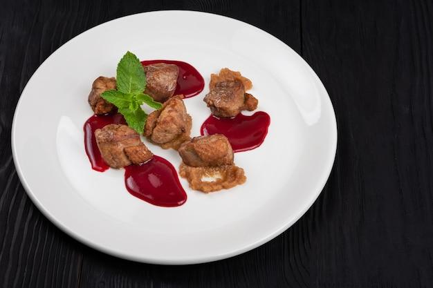 Delicadeza de carne de porco frita com purê de abobrinha e molho de frutas vermelhas decorada com hortelã no prato branco ...