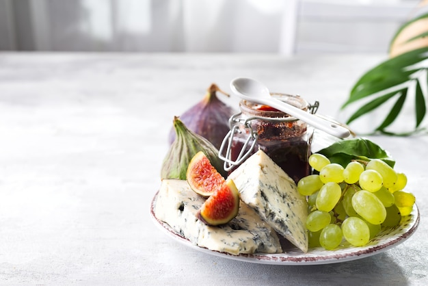Delicadeza queijos azuis, frutas e geléia no pote com folha de palmeira sobre fundo de pedra branca, copie o espaço