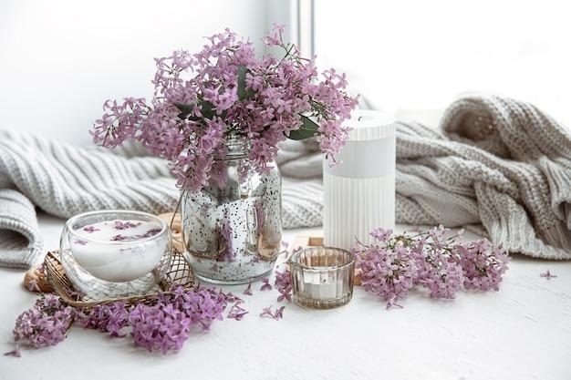 Delicado arranjo de primavera com flores em um vaso, um copo de leite e detalhes de decoração para casa.