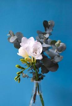 Delicado bouquet com flores brancas de reesia com ramos de eucalipto em uma superfície azul