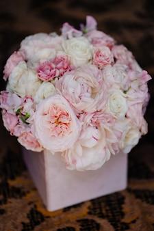 Delicado bouquet de rosas brancas e rosa em uma caixa. composição de flores para o interior e um presente para uma mulher.