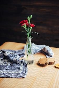 Delicado buquê de cravos em um vaso na mesa de madeira