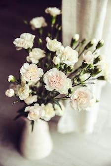 Delicado buquê de cravos em um vaso vintage. romance