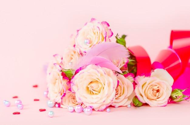 Delicado buquê de rosas peônias espessas com fitas brilhantes, pérolas, penas e corações em um fundo rosa, o conceito de parabéns no dia dos namorados