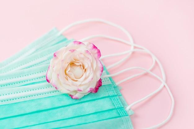 Delicado buquê de rosas peônias espessas com pérolas e máscaras de proteção facial em fundo rosa, conceito de comemorar o dia dos namorados durante o bloqueio