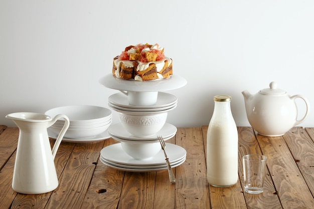 Delicado jogo de chá branco, garrafa de leite e pão de ló de dar água na boca com chocolate, creme e toranjas