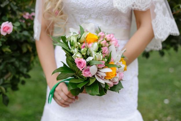 Delicado lindo buquê de casamento de rosas cor de rosa e amarelas e orquídeas com folhas verdes nas mãos da noiva close-up