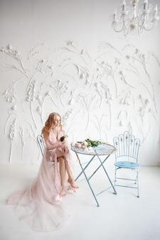 Delicado retrato de uma menina jovem modelo. a imagem da noiva, um vestido leve de renda rosa, um lindo penteado e uma maquiagem natural.