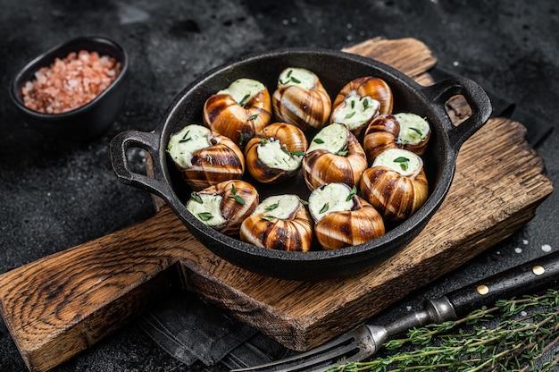 Delicatessen - borgonha escargot caracóis com manteiga de alho em uma panela. fundo preto. vista do topo.