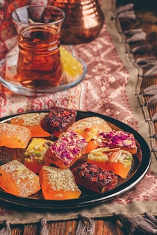 Delícia oriental rahat lokum com chá em armudu sobre toalha de mesa com enfeite