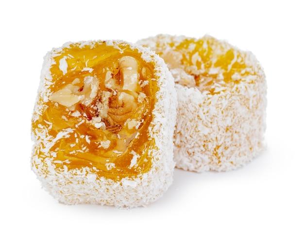 Delícia turca amarela com nozes em açúcar de confeiteiro isolado no branco