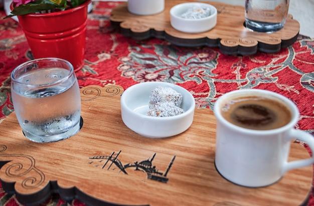 Delícia turca com uma xícara de café turco e um copo d'água na prancha de madeira