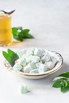 Delícia turca lokum num prato com um copo de chá