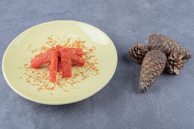 Delícia turca rahat lokum com pistache e passas secas em prato amarelo.