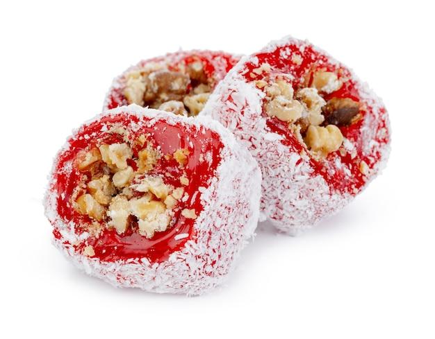 Delícia turca vermelha com nozes em açúcar de confeiteiro isolado no branco