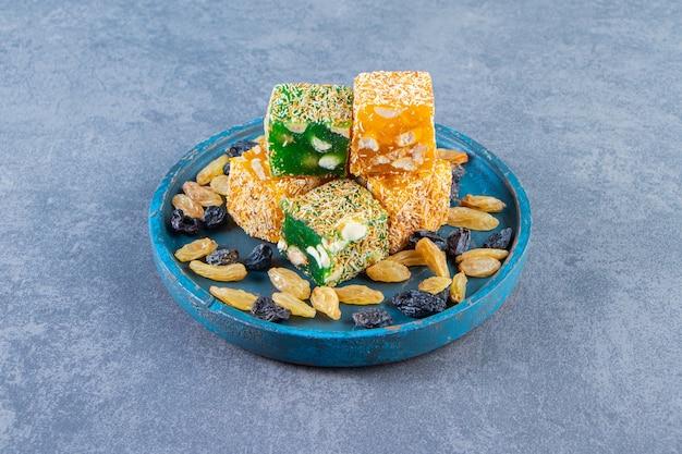 Delícias turcas e passas num prato de madeira, na superfície de mármore