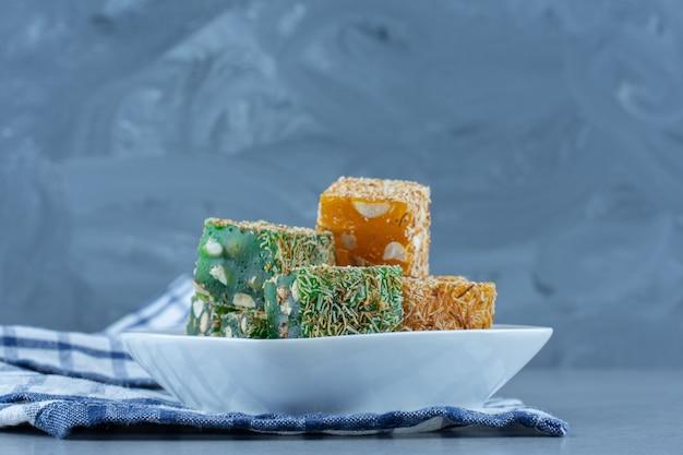 Delícias turcas verdes e amarelas na tigela sobre a toalha, na mesa de mármore.