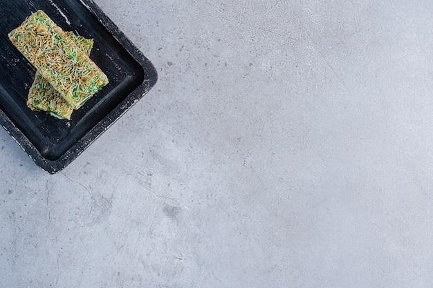 Delícias turcas verdes em uma pequena placa no fundo de mármore.