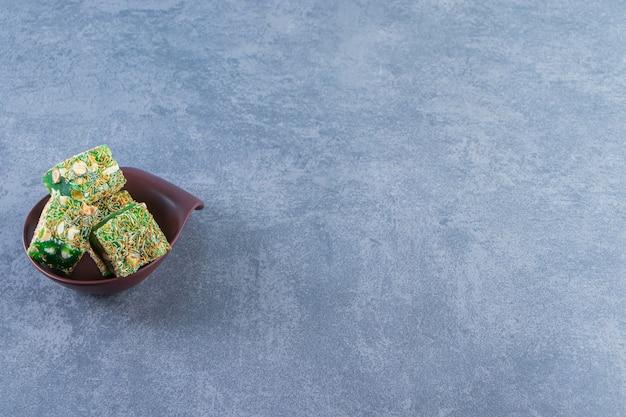Delícias turcas verdes em uma tigela, na superfície de mármore