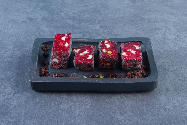 Delícias turcas vermelhas em uma placa de madeira, na superfície de mármore