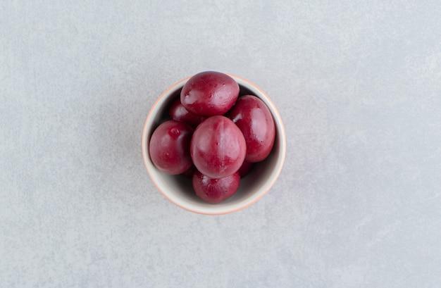 Deliciosa ameixa em conserva em uma tigela na superfície de mármore
