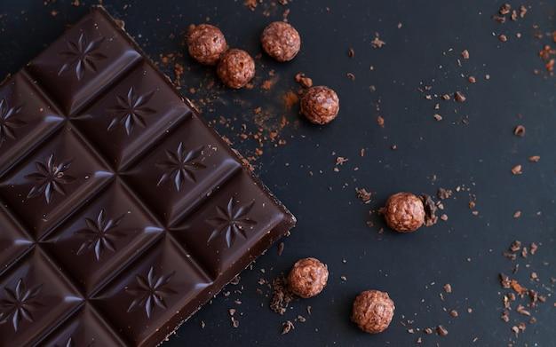 Deliciosa barra de chocolate amargo com lascas, migalhas e bolinhos de arroz em uma mesa de ardósia